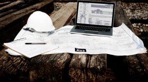 Notebook com software de gestão de obras, em cima de um projeto