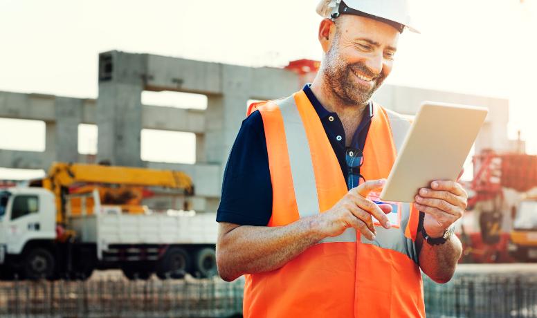 A imagem contém um engenheiro olhando satisfatoriamente para o seu tablet. Ao fundo temos um caminhão estacionado em um canteiro de obras.